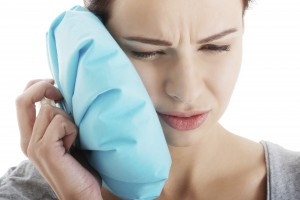 woman with mouth pain holding ice pack up to her face